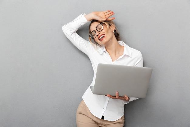 Foto van gelukkige zakelijke vrouw die een bril draagt en laptop op kantoor houdt, geïsoleerd