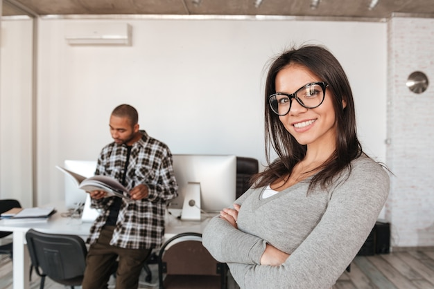 Foto van gelukkige zakenpartners die op kantoor staan terwijl man met tijdschrift en vrouw naar camera kijken met gekruiste armen. focus op vrouw.
