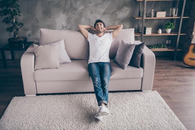 Foto van gemengd ras arabische man zitten gezellige bank hand in hand achter hoofd ontspannen huiselijke weekend stemming op zoek dromerig dragen casual outfit platte zolder woonkamer binnenshuis