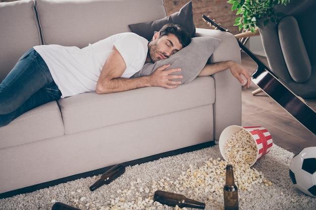 Foto van gemengd ras boozer man liggend sofa slapen kater bierfles popcorn op de vloer had gek entertainment lijden afterparty ochtend rommelig vuilnis plat binnenshuis