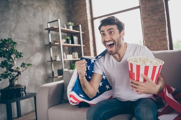 Foto van gemengd ras gekke arabische kerel zittend bank houden popcorn emmer vuisten verhogen ter ondersteuning van vs voetbalteam match amerikaanse vlag op schouders jas platte kamer binnenshuis