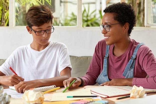Foto van gemengd ras jonge vrouwen vrouwtjes zitten samen aan tafel