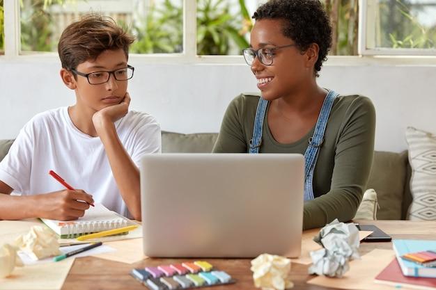 Foto van gemengd ras jongen en meisje klasgenoten kijken tutorial video samen op laptopcomputer