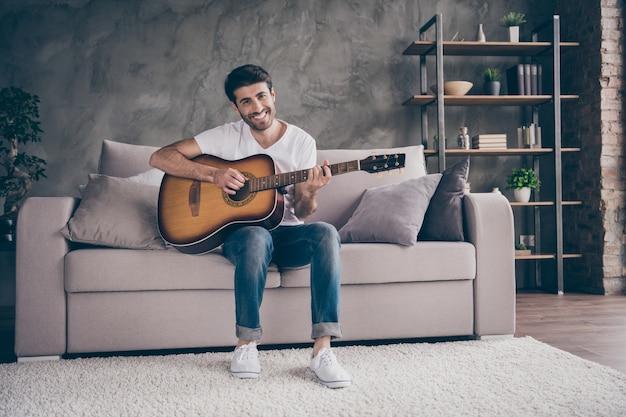 Foto van gemengd ras kerel zittend bank houden akoestische instrumentale gitaar spelen nieuw geschreven lied geluid liefde zijn hobby creatieve getalenteerde persoon platte zolder woonkamer binnenshuis