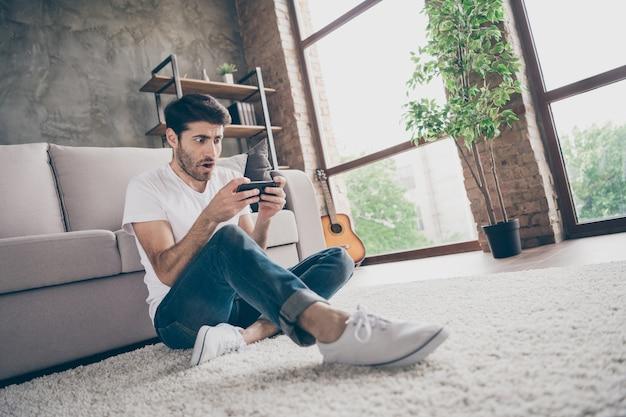 Foto van gemengd ras man zitten vloer leunende bank telefoon lezing onverwacht nieuws niet geloven ogen dragen casual outfit platte loft woonkamer binnenshuis