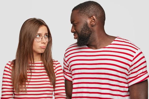 Foto van gemengd ras stel relaties uit, kijken elkaar ongenoegen aan, hebben ruzie