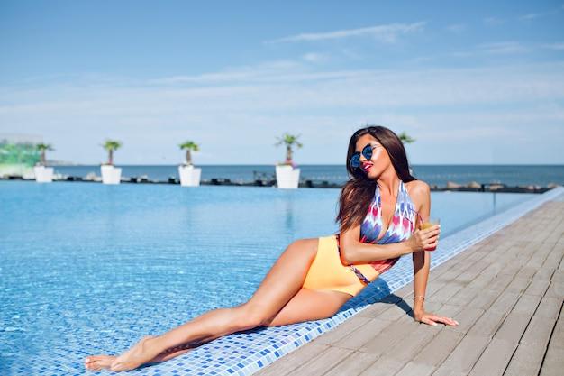 Foto van gemiddelde lengte van aantrekkelijk donkerbruin meisje met lang haar dat dichtbij pool ligt. ze houdt een cocktail vast en lacht.