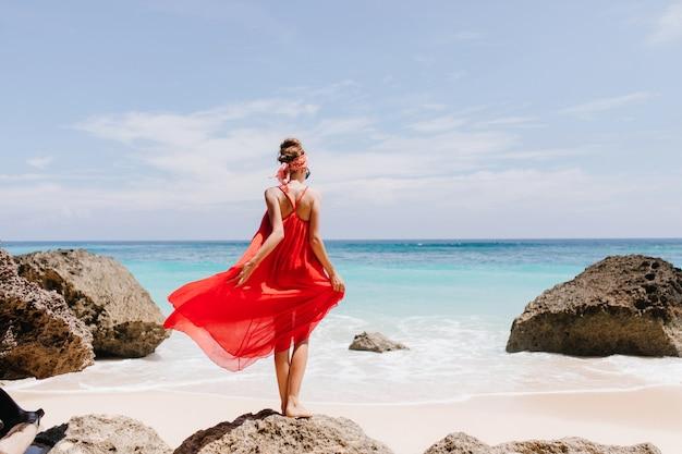 Foto van gemiddelde lengte van achterkant van vrij vrouwelijk model dat zich op grote steen op oceaan bevindt. openluchtportret van blije slanke vrouw in rode jurk die horizon in winderige dag bekijkt.