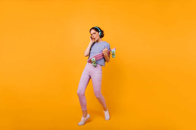 Foto van gemiddelde lengte van dansende glamoureuze dame met longboard. portret van geweldige blanke vrouw poseren in koptelefoon en muziek luisteren.