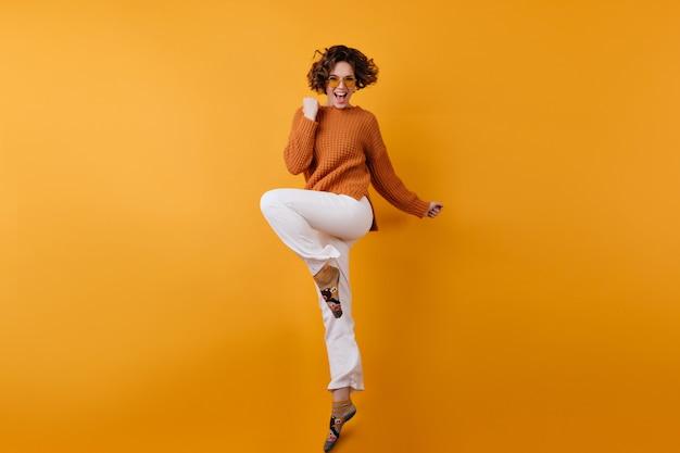 Foto van gemiddelde lengte van elegant europees vrouwelijk model dat van opwinding danst
