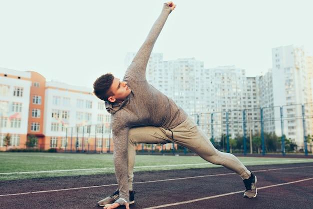 Foto van gemiddelde lengte van jonge kerel bij training in de ochtend op stadion. hij draagt een grijs sportpak. hij doet oefening.