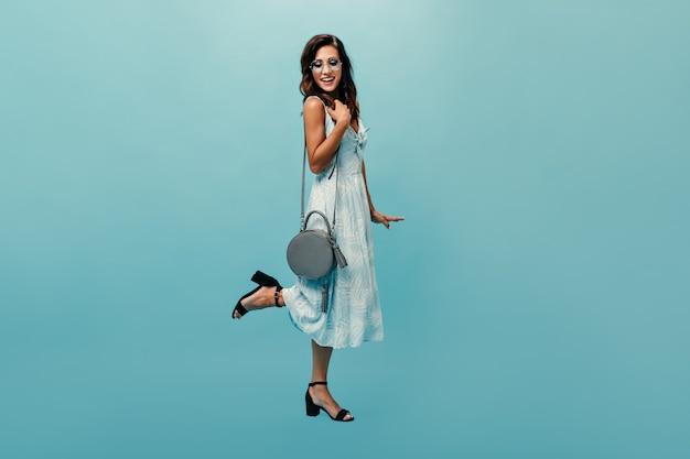 Foto van gemiddelde lengte van meisje in blauwe sundress met modieuze zak op geïsoleerde achtergrond