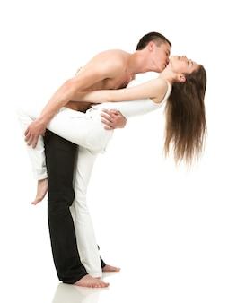 Foto van gemiddelde lengte van paar knuffelen terwijl ze staan. man in zwarte spijkerbroek en holm torso, meisje in witte kleren