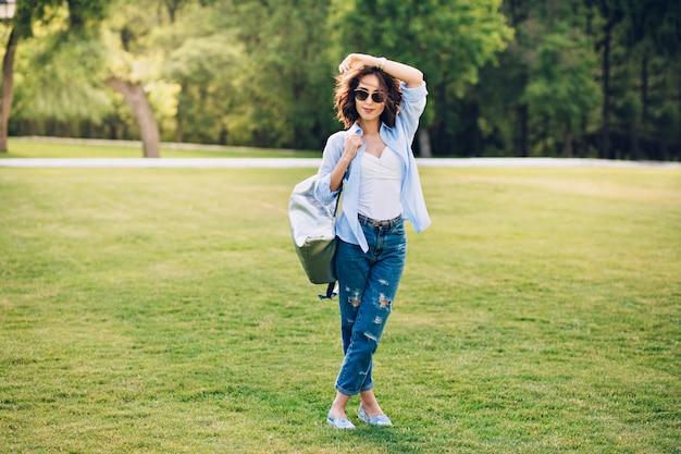 Foto van gemiddelde lengte van schattige brunette meisje met kort haar in zonnebril poseren in park. ze draagt een wit t-shirt, een blauw shirt en een spijkerbroek, schoenen, tas. ze lacht naar de camera.