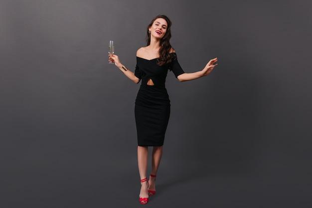 Foto van gemiddelde lengte van vrouw in zwarte passende jurk en op hoge hakken die zich voordeed op zwarte achtergrond met een glas champagne in haar handen.