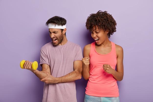 Foto van gemotiveerde blanke man heft arm op met zware halter, werkt aan spieren, ondersteunende vrouw met donkere huid balde vuisten en roept, gelooft in succes van vriendje. sportprestaties