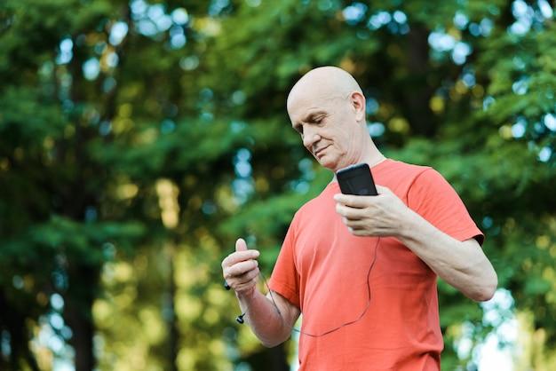 Foto van gepensioneerde gepensioneerde draagt een koptelefoon terwijl hij naar muziek luistert en probeert af te luisteren in het park. hoge foto