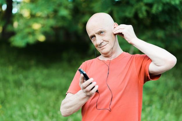 Foto van gepensioneerde gepensioneerde draagt een koptelefoon terwijl hij naar muziek luistert en probeert af te luisteren in het park.