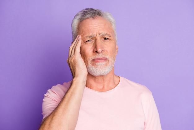 Foto van gepensioneerde opa hand hoofd vermoeide blik camera draagt roze t-shirt geïsoleerd violet kleur achtergrond