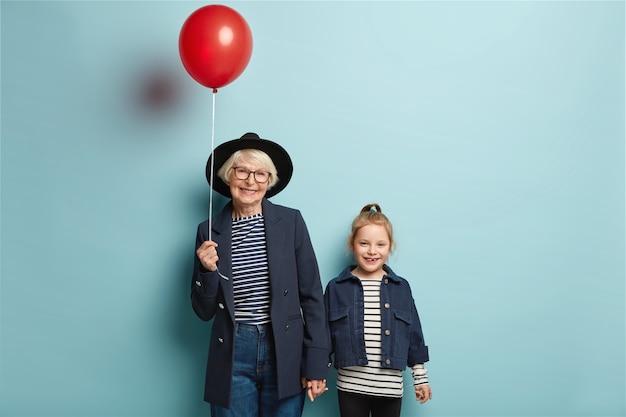 Foto van gepensioneerde senior vrouw houdt hand van kleine schattige kleindochter, kom op feestje, houdt rode ballon