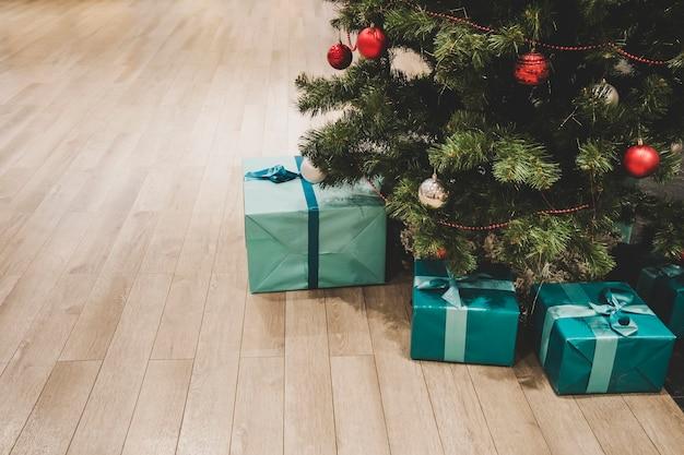 Foto van geschenkdozen onder de kerstboom, huisdecoratie voor het nieuwe jaar, inpakken van kerstcadeaus, festivalspar versierd met slinger, kerstballen en speelgoed, traditionele viering.