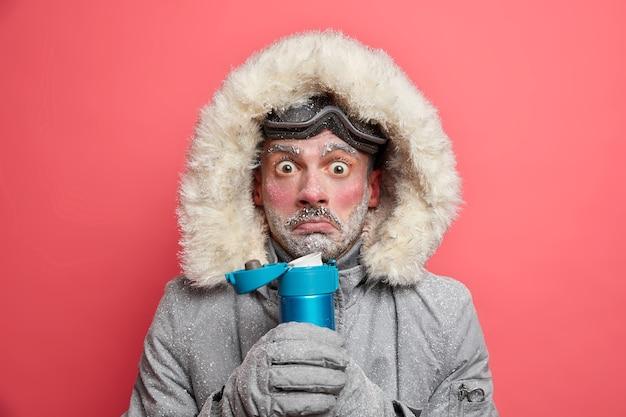 Foto van geschokt beschaamd man beeft van kou besteedt veel tijd buiten tijdens ijzig weer, dranken hete thee houdt thermosfles draagt outfit voor wintersport.
