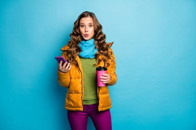 Foto van geschokt dame houden warm papier drank mok browsen telefoon lezen nieuws dragen gele overjas sjaal violet broek groene trui geïsoleerde blauwe kleur muur