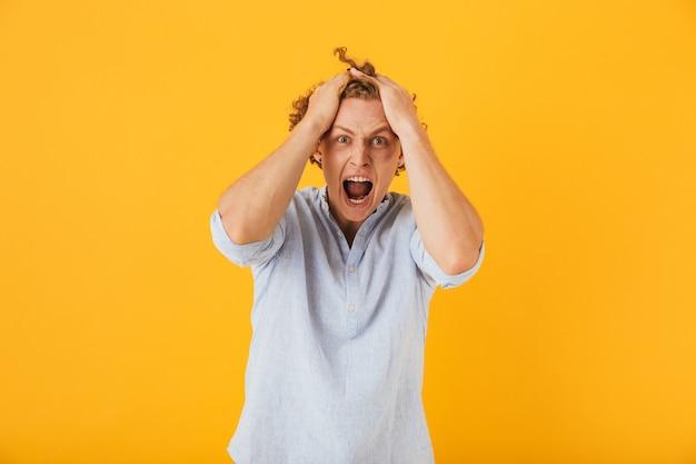 Foto van geschokt jongeman met krullend haar hoofd grijpen en schreeuwen in woede, geïsoleerd op gele achtergrond