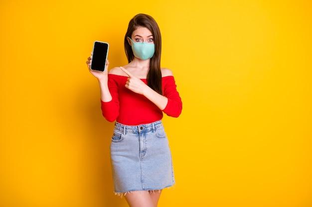 Foto van geschokt meisje hipster in medisch masker wijsvinger smartphone aanwezig covid quarantaine advertenties promo draag rode top korte minirok geïsoleerd over heldere glans kleur achtergrond