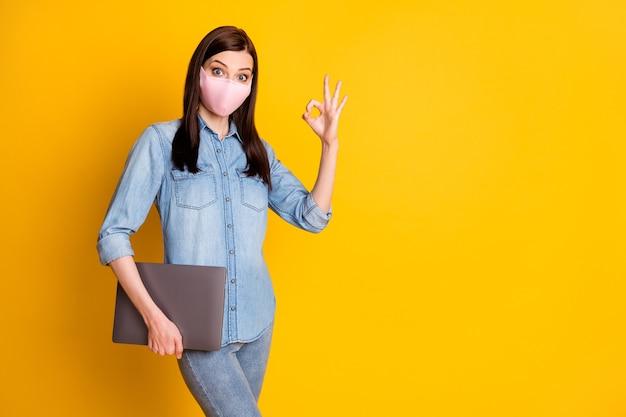 Foto van geschokt meisje houdt laptop vast en laat goed teken zien