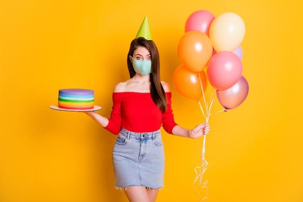 Foto van geschokt meisje met medisch masker vieren covid verjaardag gelegenheid houd ballon verjaardagstaart draag korte mini spijkerbroek rok rode top geïsoleerde heldere glans kleur achtergrond