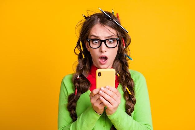 Foto van geschokt meisje potlood kapsel lees studie examen mobiele telefoon dragen shirt geïsoleerd felle kleur achtergrond