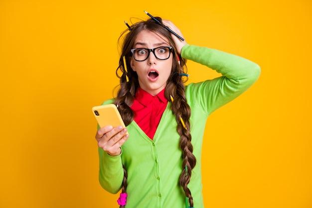 Foto van geschokt meisje rommelig kapsel houdt smartphone schreeuw geïsoleerd glans kleur achtergrond