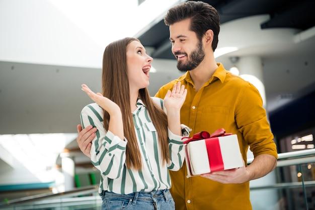 Foto van geschokte aantrekkelijke dame knappe kerel paar onverwachte verrassing geschenkdoos verjaardag datum gelegenheid bezoek winkelcentrum winkel samen dragen casual jeans shirt outfit binnenshuis