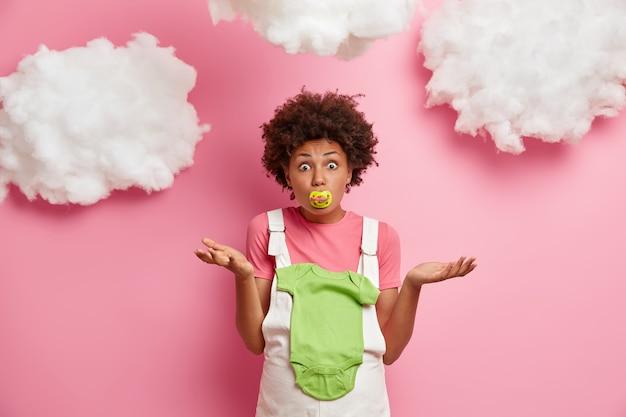 Foto van geschokte aarzelende aanstaande moeder weet het geslacht van de toekomstige baby niet, poseert met bodysuit op buik en tepel in de mond, staat binnen verward. familie, moederschap en ouderschap concept