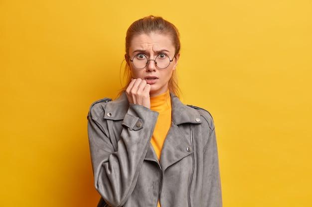 Foto van geschokte bezorgde vrouw verbaasd over slecht nieuws, kijkt zenuwachtig, staat angstig, gekleed in grijs jasje