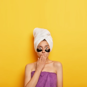 Foto van geschokte europese vrouw bedekt mond met handpalm, past pleisters onder de ogen toe om rimpels te verwijderen, neemt regelmatig een bad, wil een perfecte huid hebben