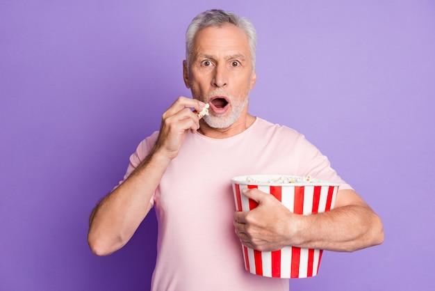 Foto van geschokte grootvader omhelst papieren emmer eet popcorn nerveus draag roze t-shirt geïsoleerd violet kleur achtergrond