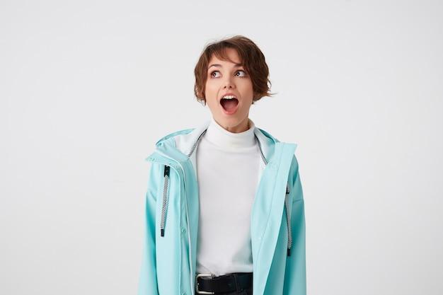 Foto van geschokte kortharige krullende dame in witte golf en lichtblauwe regenjas, staat op witte achtergrond met wijd open mond en verbaasde uitdrukking, kijkt weg met wijd open ogen.