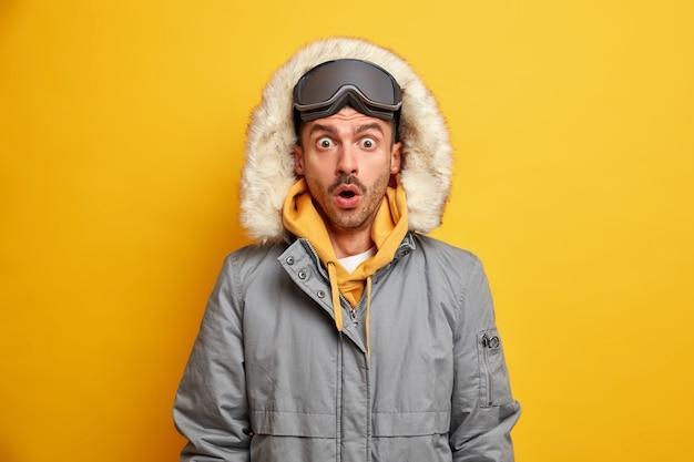 Foto van geschokte man skiër staart sprakeloze jurken warm voor koude winterweer draagt skibril.