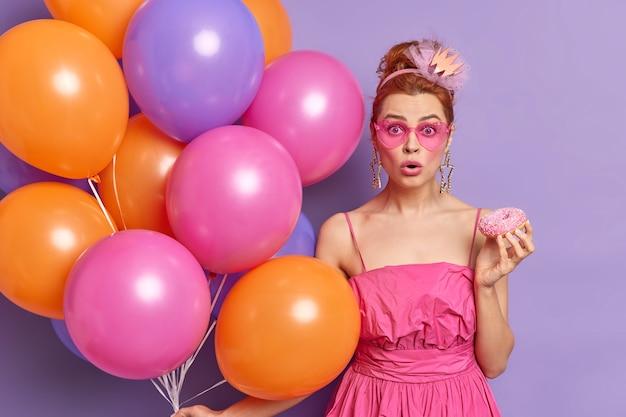 Foto van geschokte roodharige vrouw staart door roze tinten met smakelijke geglazuurde donut met veelkleurige ballonnen ontdekt schokkend nieuws