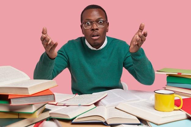Foto van geschokte zwarte man steekt zijn handen in verbijstering op, heeft wijd geopende ogen, gekleed in een groene trui, vertaalt buitenlands artikel, gebruikt veel dikke woordenboeken