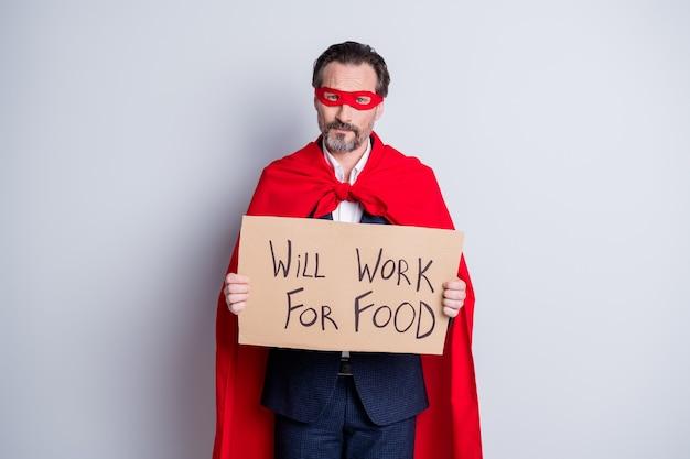 Foto van gestresste ontevreden serieuze bedelaar volwassen ontslagen zakenman superheld kostuum houd karton plakkaat nodig baan werkkleding pak rood gezichtsmasker mantel geïsoleerde grijze achtergrond