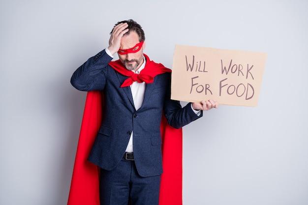 Foto van gestresste verontruste bedelaar volwassen ontslagen zakenman superheld karakter kostuum houd karton plakkaat nodig smeken vragen werk dragen pak rood gezichtsmasker mantel geïsoleerde grijze achtergrond