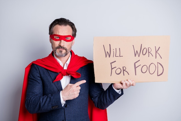 Foto van gestresste volwassen ontslagen zakenman superheld karakter kostuum direct vinger karton plakkaat moet smeken vragen baan werkkleding pak rood gezichtsmasker mantel geïsoleerde grijze achtergrond
