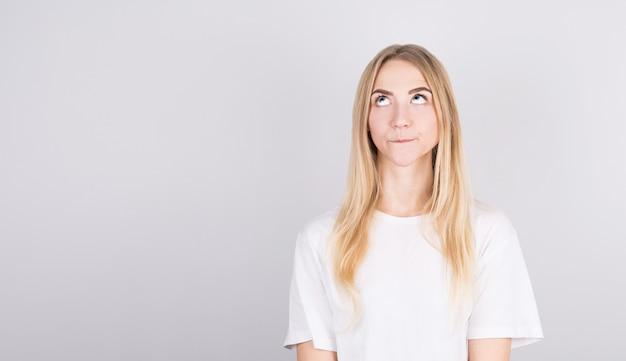 Foto van geweldig blond meisje opzoeken lege ruimte diep denken geïsoleerd op een grijze achtergrond