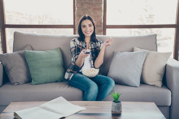 Foto van geweldige dame gaat kijken naar favoriete humor tv-show met afstandsbediening en popcorn plaat zitbank dragen casual kleding appartement binnenshuis