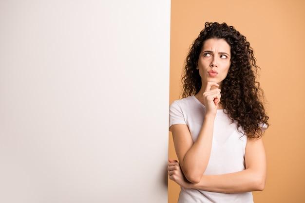 Foto van geweldige dame op zoek met twijfels over lege korting banner grote witte plakkaat beslissen wat te schrijven dragen casual kleding geïsoleerde beige pastel kleur achtergrond