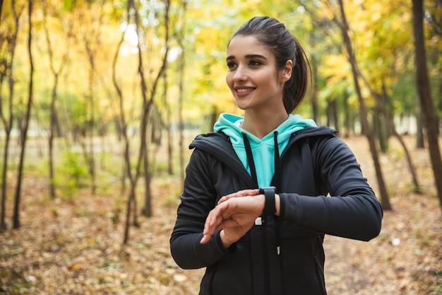 Foto van geweldige jonge mooie fitness vrouw buiten in het park horloge klok kijken.