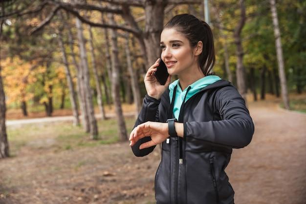 Foto van geweldige jonge mooie fitness vrouw buiten in het park horloge klok praten door mobiele telefoon kijken.